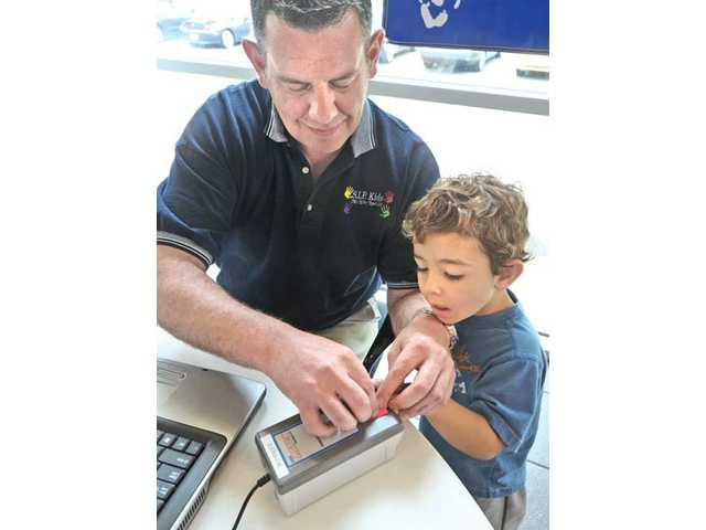 S.I.P. Kids Child Safety Specialist Jeff Jackson, left, prepares to fingerprint Charlie Gadbois, 3, of Saugus as part of the Keeping Kids Safe Project which provides FBI quality digital fingerprints and photos of children to their parents at no charge.
