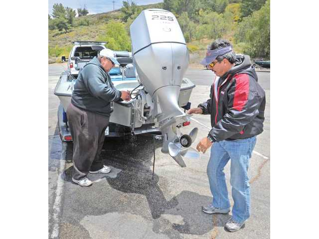 Bass fisherman Hugh Mitchell, left, and Bobby Nelson release water from their bass boat as part of the clean and dry procedures that kill quagga mussel larvea after a day of fishing at Castaic Lake in Castaic on Saturday.
