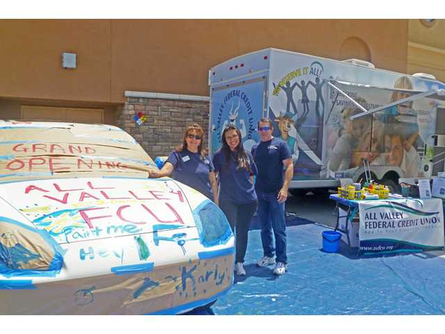 Celebrants at the grand opening of the All Valley Federal Credit Union in Santa Clarita had a chance to create mobile art by painting on a vehicle donated by Valencia BMW. AVFCU executives, from left, Cecelia Zumbado, Kelly Cobos and Mark Davey kicked off the celebration by inviting guests to paint on the car.