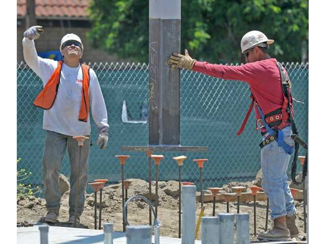 Workers guide a crane operator placing a column at the west side of Old Town Newhall Library in Newhall on Tuesday.