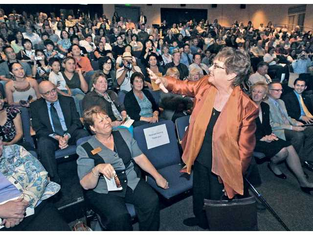 Judy Fish, superintendent of the Saugus Union School District, standing, waves her arm as she describes her surprise at seeing the hundreds of faces when she entered the Santa Clarita Performing Arts Center at College of the Canyons for the inaugural Festival of Music.