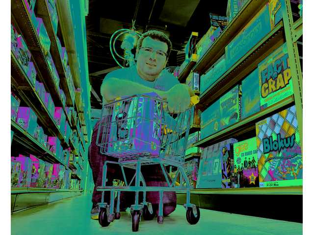 Jay Demircift, owner of Puzzle Zoo, located inside the Valencia Town Center Mall, kneels down in one of the toy isles in his store with a tiny shopping cart full of toys.