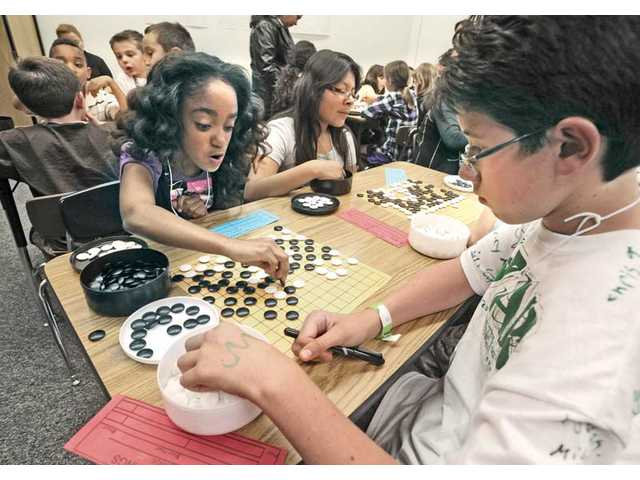Sixth graders Sharene Nance, left, and Ian Pinero, right, play each other.