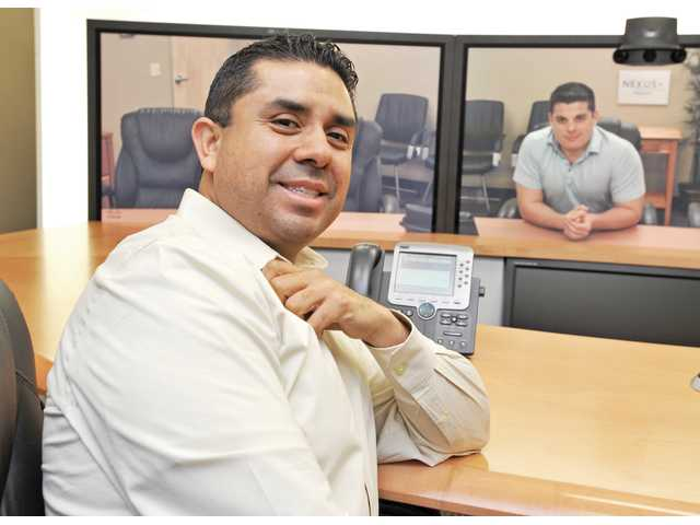 Brian Castillo, marketing operations manager for Nexus IS Inc., left, poses in the company's Valencia headquarters with account manager Zack Danna, appearing through a Cisco TelePresence unit from Pleasanton on Monday.