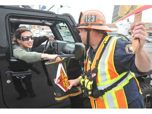Capt. Mark Whaling, right, of Engine Company 123 accepts a donation in a firefighter's boot from passing motorist Erin Ferrell, of Valencia, at the corner of Sierra Highway and Soledad Canyon Road in Canyon Country. Firefighters from 12 local fire stations collected thousands of dollars through the Fill the Boot for Jerry's Kids campaign for muscular dystrophy Thursday, Friday and Saturday in Santa Clarita.