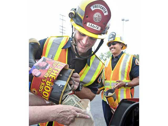 Firefighter Sven Michaelson, left, and engineer John Guinto of Engine Company 132 combine the donations they collected at the corner of Sierra Highway and Soledad Canyon Road in Canyon Country as part of a Fill-The-Boot effort for the Jerry's Kids campaign for the fight against muscular dystrophy. See A6 for more pictures.