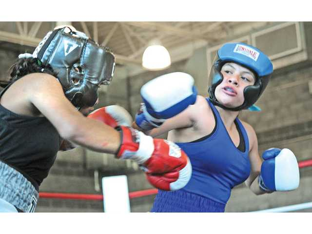 Tiffany Ocampo, 12, right, of Santa Clarita Boxing Club lands a punch on Esperanza Ruelas, 12, of Santisima Boxing during their bout at the USA Boxing Inc., Santa Clarita Boxing Club Show held at the Santa Clarita Community Center in Newhall on Saturday. Ocampo lost the match.