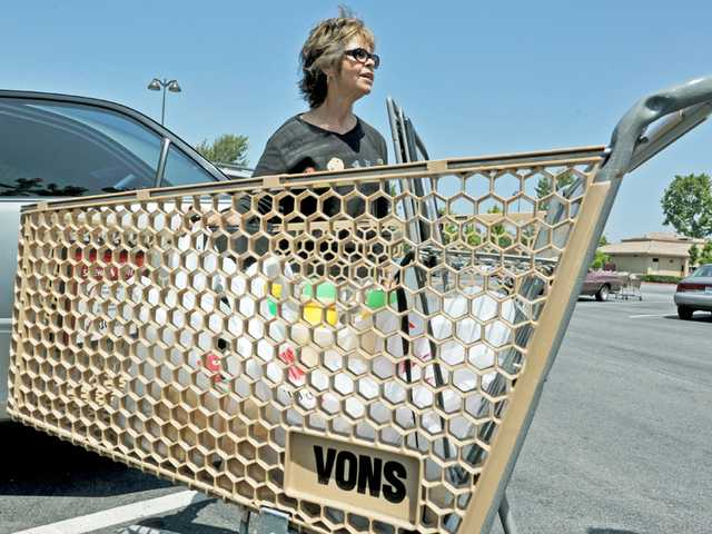 Margaret Rummell expresses her concern about a possible supermarket strike as she loads groceries into her car on the Vons parking lot in Saugus on Monday.
