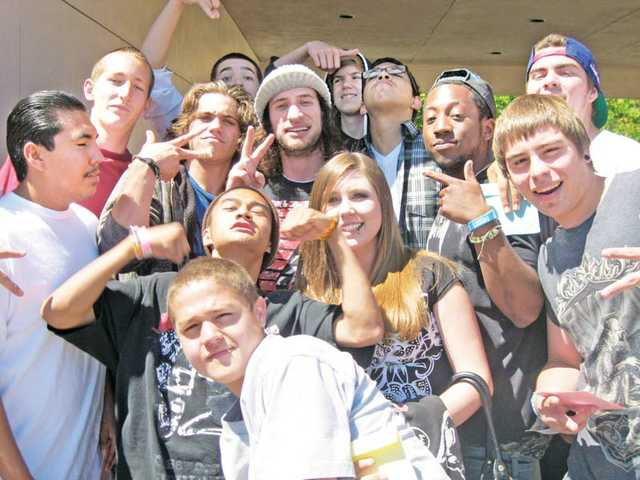 Brian Bell, center with hat,  poses with Bowman High School students during a concert on May 20. The performing artist also met signed autographs and gave away free tickets to his concerts.
