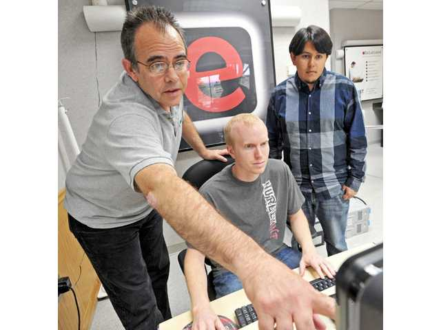 Owner John Duncan, left, oversees a project with back-end programmer Karl Pierce, middle, and designer and integrator Alfredo Torres at eSolutions storefront in Saugus.