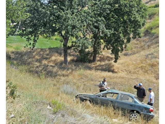 A California Highway Patrol officer and golf course personnel investigate the scene where a woman driving a Kia Sephia crashed through a fence after driving  northbound The Old Road. The Sephia came to a rest on the Tournament Players Club Valencia in Valencia on Tuesday. No injuries were reported.