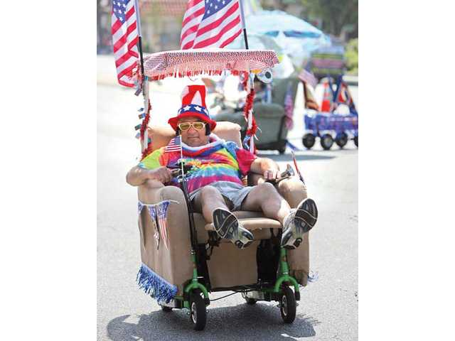 A member of the Lazy Boys, of Santa Clarita, rides his chair down Lyons Avenue for the Santa Clarita Valley Fourth of July Parade last year. This year's deadline for participation in the parade is Sunday.