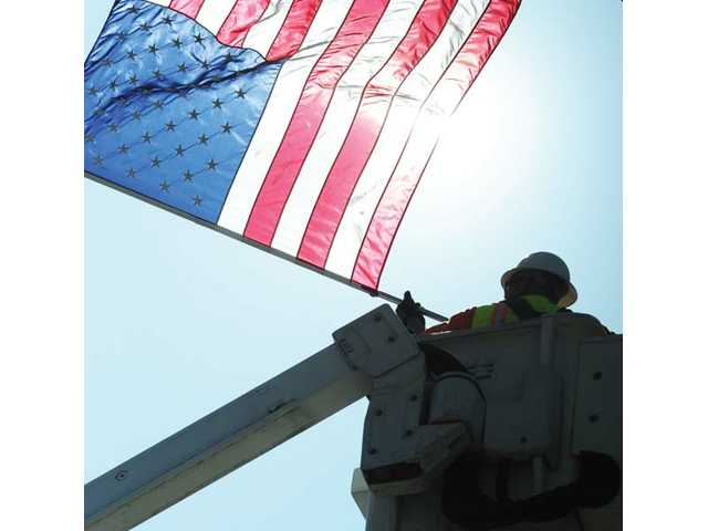 Robert Griego, a street-maintenance worker, works from a cherry picker Wednesday as he takes down flags that were raised in Santa Clarita on Tuesday for Flag Day.