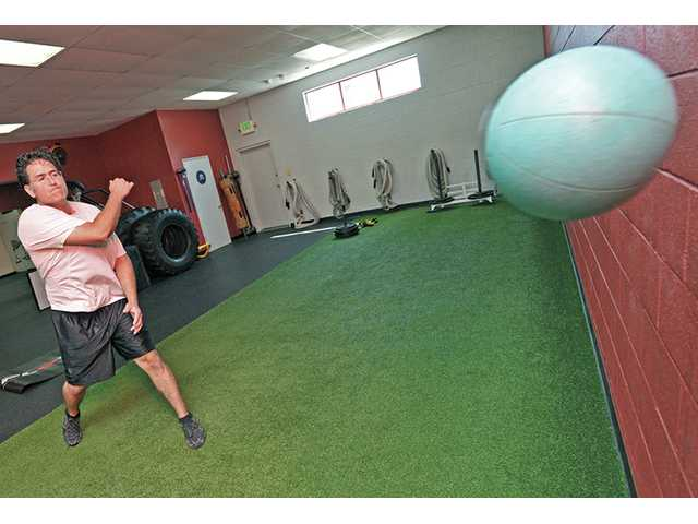 Hector Quinonez demonstrates a medicine ball side toss.