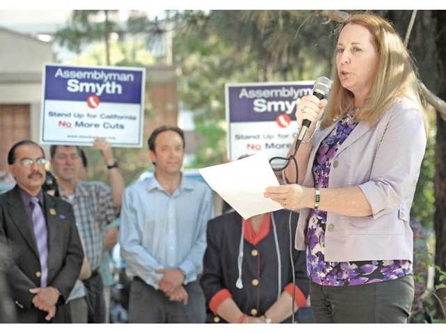 Local resident Linda Alexander-Lieblang, right, representing the Alzheimer's Association addresses a group of about 50 people made up of Los Angeles County employees and concerned citizens who met in front of the office of Assemblyman Cameron Smyth in Valencia on Tuesday evening.