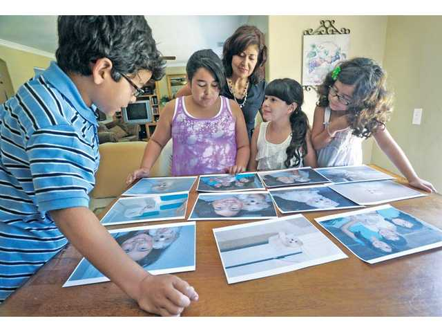 "Dan Members of the Afetian Family, from left, Alex, 8; Cassandra, 12; mother, Kathryn Christina, 10; and Olivia, 5, go through photos of their 1-year-old ""Mal-Shi"" dog, Bella was apparently killed in backyard by a coyote that jumped their fence in Fair Oaks Ranch in Canyon Country."