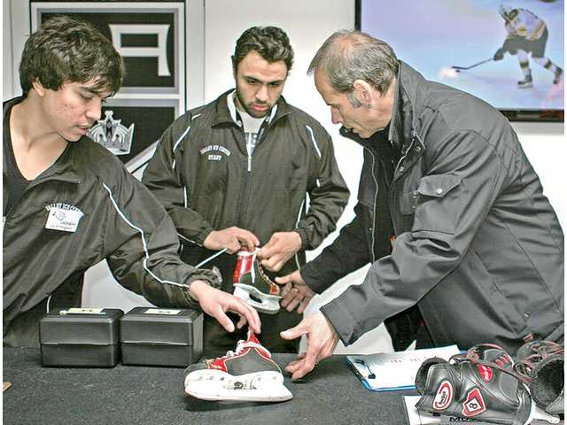 Lloyd Eisler, right, director of  skating operations at the L.A. Kings Valley Ice Center in Panorama City, works with employees at the rink. Eisler is also a figure skating coach.