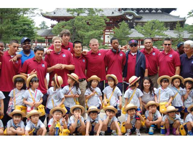 J.C. Cloney, Ryan Keller and other members of the USA Friendship Series baseball team pose with a group of kids at a Buddhist Temple outside of Osaka, Japan.