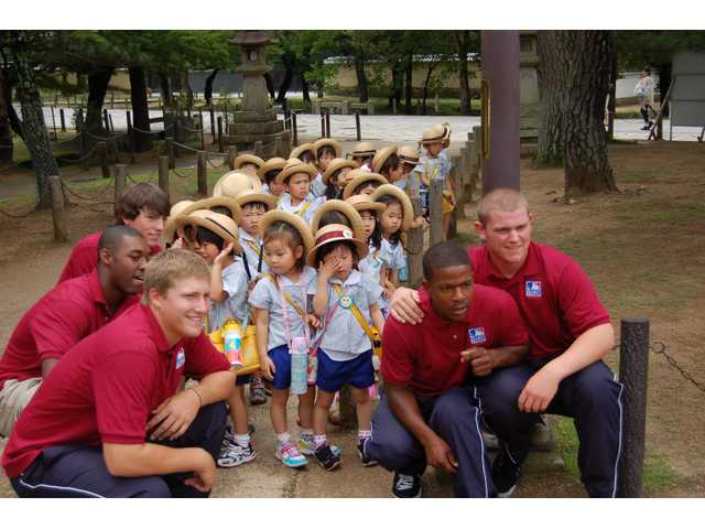 Ryan Keller, front left, and J.C. Cloney, far right, pose with teammates and kids at a Buddhist Temple outside of Osaka, Japan.