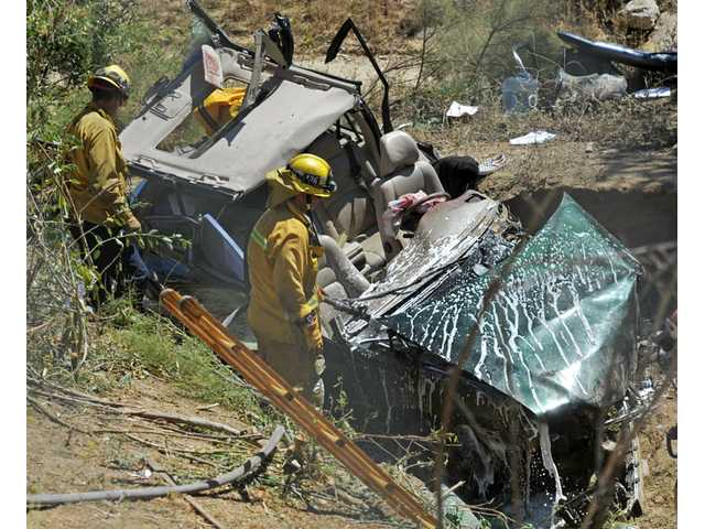 Los Angeles County firefighters clean up and survey the scene where a Volvo V70 was driven into an embankment, next to the Valencia Boulevard offramp, after traveling northbound Interstate 5 in Valencia on Tuesday.