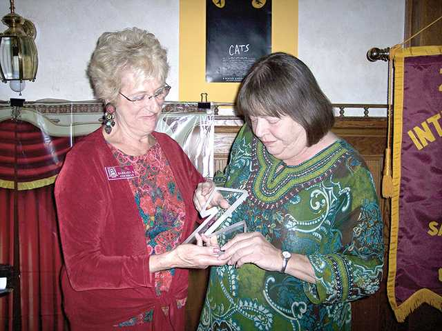 Jami Kennedy, right, is presented with the Zontian of the Year trophy by head of the selection committee, Barbara Cochran.