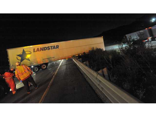 A hazmat crew supervises the removal of a big rig from the shoulder of Interstate 5, where it crashed late Wednesday night, snarling I-5 traffic for several hours.