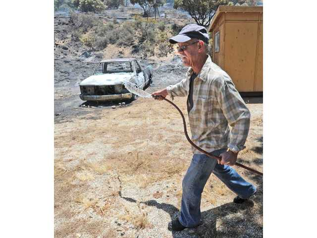 Acton resident Bill Boyd wets down the brush around his Hubbard Road property and mobile home after fire burned his 1984 Chevrolet truck and tool shed in a 100 acre brush fire in Acton on Thursday.