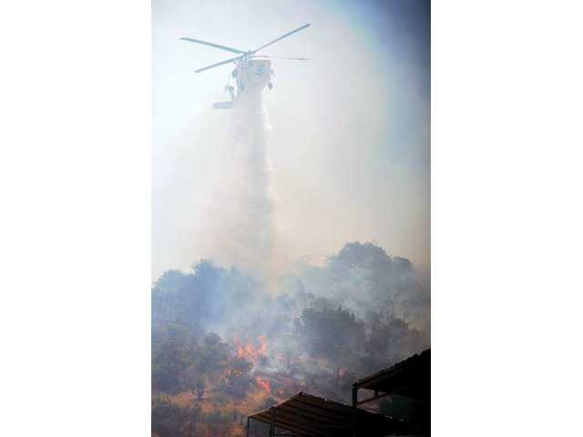 A water dropping helicopter makes a drop on flames that burned near a home and out-buildings in the 6300 block of Hubbard Road in a 100 acre brush fire Acton on Thursday.