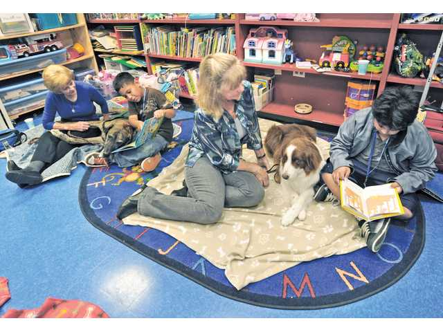 Angel Castro, 8, left, and Jonathan Gonzalez, 10, read to Santa Clarita Therapy Dogs, Sparky, left, and Merced at the Santa Clarita Community Center in Newhall on Wednesday. Owners Sharon Rendall, left, Chris Talbott  listen as the children read from their books.