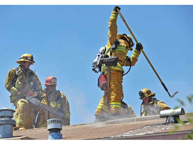 Los Angeles County firefighters puncture the roof of a mobile home to ventilate a fire that was confined to the unit's bathroom at the Royal Oaks Mobile Park in Canyon Country on Thursday.