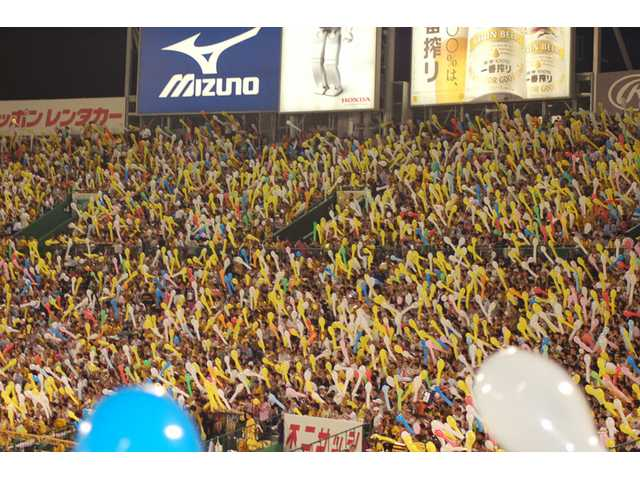 Fans attending a game between the Hanshin Tigers and the Tokyo Giants at Koshien Stadium prepare to let balloons into the air during the middle of the seventh inning.