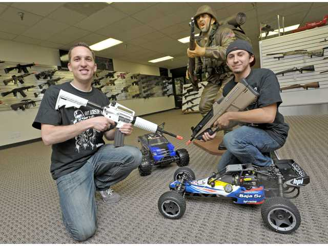HobbyTron Vice President Ben Ibarra, left, and airsoft specialist Luke Saenz carry airsoft guns as they pose among remote-controlled trucks at the storefront.