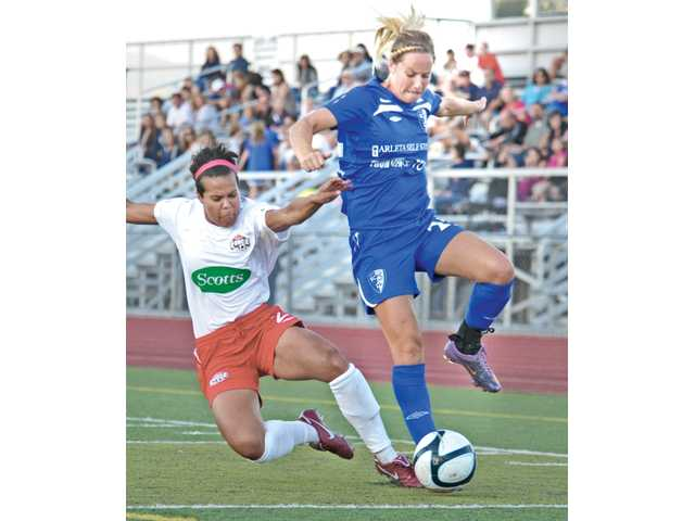Santa Clarita Blue Heat forward Hannah Beard, right, tries to protect the ball from the sliding tackle of Colorado Force defender Jenifer Thomas on Tuesday at Valencia High School. The Blue Heat beat the Force 3-1 in their W-League game.