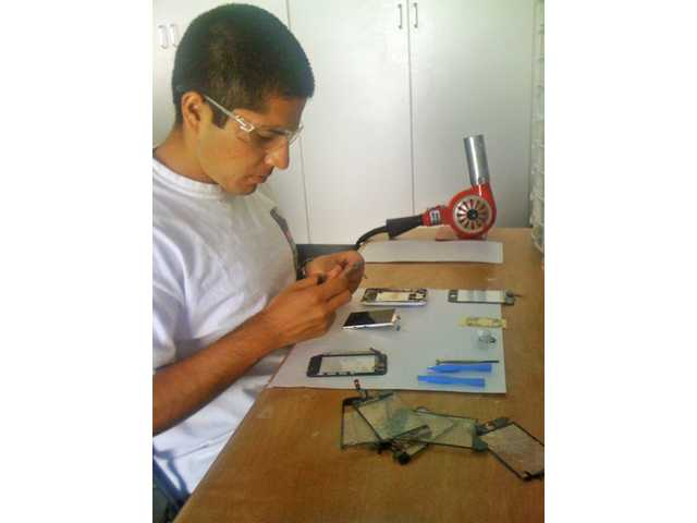 Alan Campos of SCViRepair fixes an iPhone at his home work station. Campos fixes iPhones and iPods for a fraction of the cost charged by retail stores.