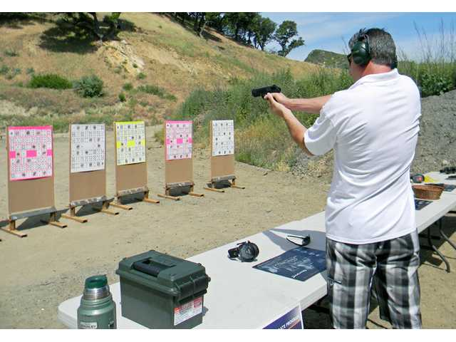 Eric Stroh takes a turn at a new event held at this year's trap shoot. The opportunity to shoot a Beretta Px4 handgun.