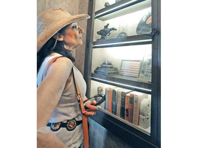Leslie Lopata, of Encino, examines the artifacts on display as she takes a guided tour of the William S. Hart Museum.