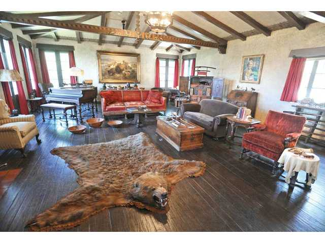 The living room remains just as it did when silent movie star William S. Hart lived in the house, decorated with a Charles M. Russell oil painting, center, and an Alaskan Kodiak bearskin rug that was given to Hart as a house-warming gift by Will Rogers in 1927.