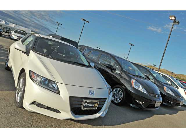 New cars sit on the lot at Power Honda Valencia. As summer heats up, gas prices and the sales-tax rate are falling.