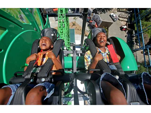 Madison Spell, 9, and her brother Michael, 11, of Santa Clarita, react as they ride on Green Lantern: First Flight at Six Flags Magic Mountain in Valencia on Thursday. The new ride opens to the public today at the theme park.