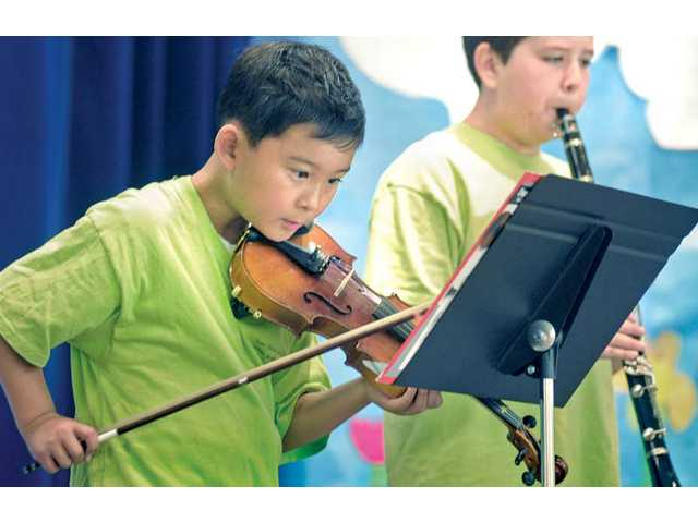 "Shane Park, left, follows along with the music as Christopher Mildon plays ""Twinkle, Twinkle, Little Star"" at the Saugus Union School District's Summer Arts Showcase 2011 held at Rosedell Elementary School in Saugus on Thursday."