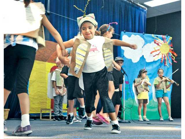 "Nicole Lerma, 7, dressed as a bug, dances with her classmates as they perform in the play ""The June Bug and the Flea."""