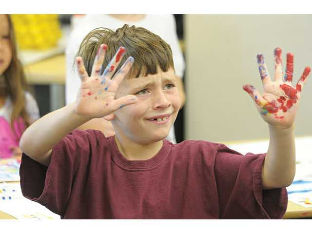 Ethan Coppess, 7, displays his paint-covered hands as he waits for a paper towel June 22. Ethan painted his impressions while listening to classical music as part of the academic enrichment program at Tesoro del Valley Elementary School in Valencia.