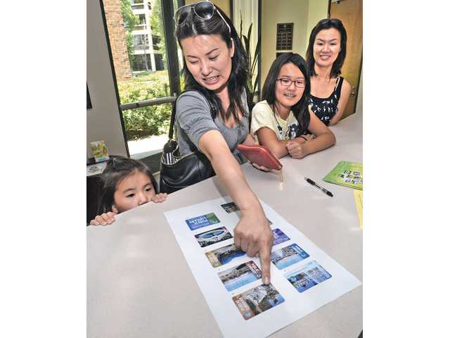 Kyung Lee, center, points to designs offered for the new Santa Clarita Public Library card as daughters Grace, 5, left, and Crystal, 10, try to decide which design they want as they register for the new library card at City Hall on Wednesday. Angie Kang, far right, looks on.