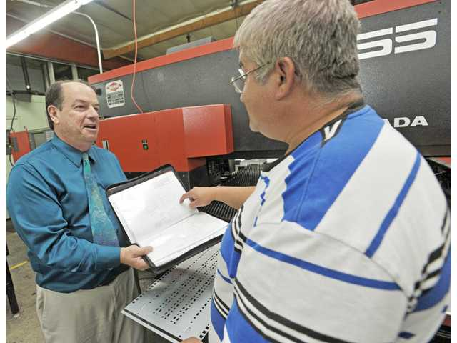Bert Braché, owner of Loop Aerospace, and Gilberto Padilla look over schematics in a sheet-metal plant, one of the many aircraft parts manufacturing facilities Brache's company works with.