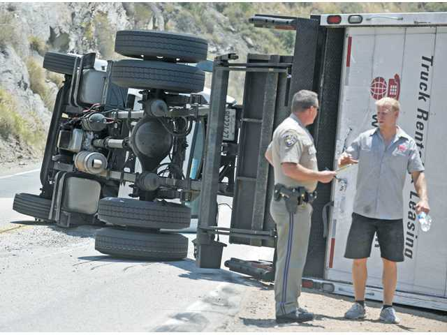 California Highway Patrol Officer B. Kelley, left, speaks with truck driver Nicholas Hunter behind the box truck that Hunter was driving on San Francisquito Road, approximately five miles north of Copper Hill, in the Angeles National Forest on Tuesday.