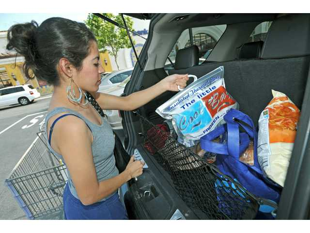 Azucena Vargas, of Valencia, loads reusable bags into her car outside of Albertsons, on Copper Hill Drive, in north Valencia on Tuesday.