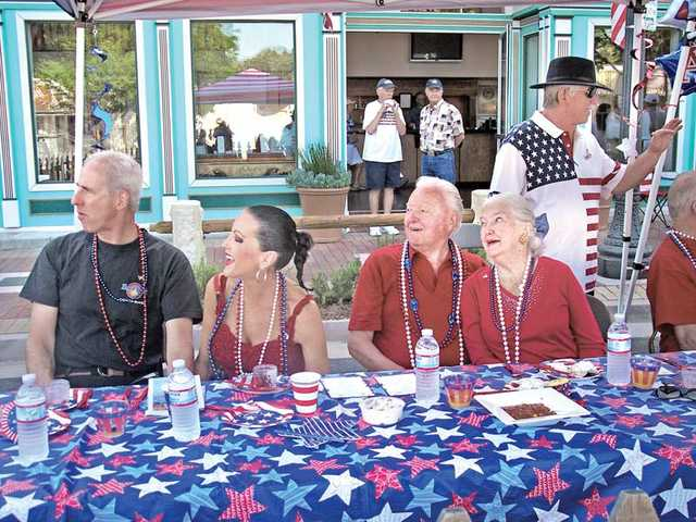 Right to left, G. Marshall and Shelley Hann and Harold and Jacqulyn Petersen have front-row seats at the annual Fourth of July Parade in front of the Canyon Theatre Guild.