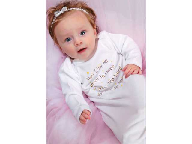 Baby Sophia models Heaven Sent's infant nightgown. All infant wear sold by the wholesaler has spiritual, faith-based messages on the apparel.