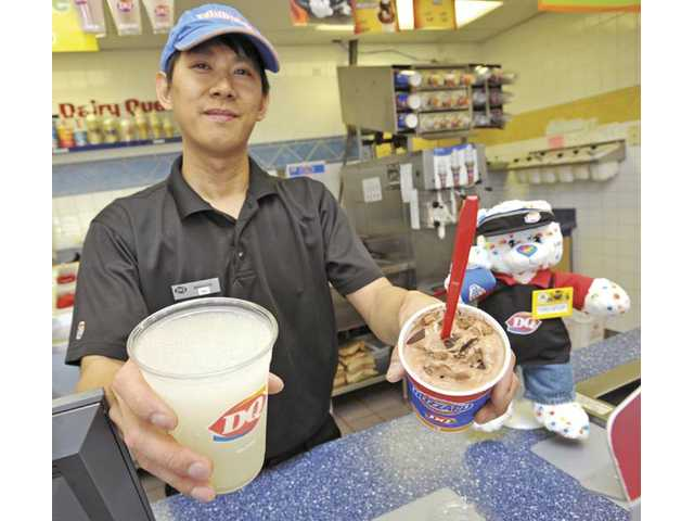 Manager Frans Kam shows a Lemonade Chiller and a Triple Chocoholic Blizzard at Dairy Queen in Saugus.