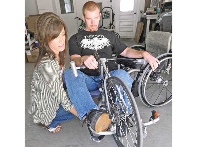 With the help of his wife, Kevin Mather practices hand-cycling.